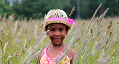 little girl playing in a field in tall grass